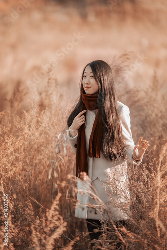 002274c1e313 A beautiful Asian girl in Marsala scarf and gloves in an Autumn ...