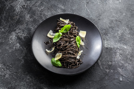 Black pasta (squid ink) with lemon pepper sauce, basil leaves, parmesan  in a black plate on a dark background. Flat top view.