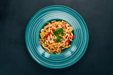Pasta with mushrooms and vegetables. Italian cuisine. On a wooden background. Top view. Copy space.