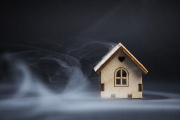 Wooden decorative toy house standing in winter blizzard on black background. Purchasing or buying a house or rental of property, cosy home and new house for children concept
