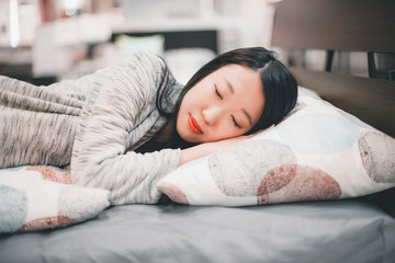 Close portrait of beautiful young asian girl in gray sleeping on a bed with light white pillow with print
