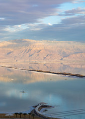 Sunset over lowest salty lake in world below sea level Dead sea, full of minerals near luxury vacation resort Ein Bokek, perfect place for medical treatments