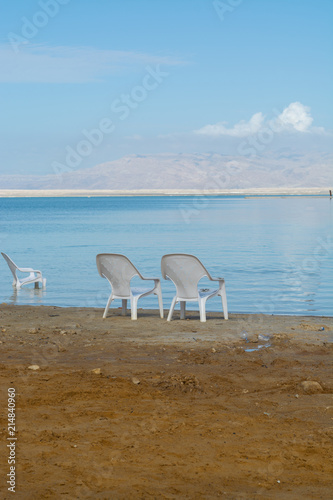 Two white plastic chairs on lowest salty lake in world below