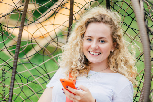 Satisfied blonde young female with curly hair, has positive smile