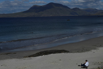 A man in a suit sits on the beach in the Connemara village of Renvyle