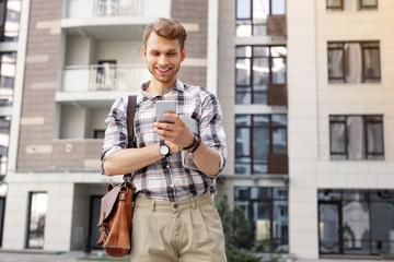 Digital media. Happy joyful man smiling while looking at his smartphone screen