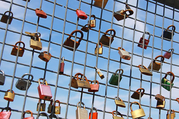 collection of love & friendship padlocks mounted on a grate against blue sky