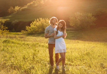 Stylish young couple. Film photo at sunset and with a sunlight. A blond guy with long hair pulls a red-haired girl. A loving couple walks along the spring, green hills