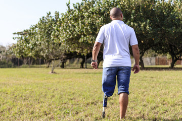 Man amputated with prosthesis contemplating outdoor landscape