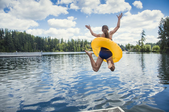 A little girl jumping off the dock into a beautiful mountain lake. Having fun on a summer vacation