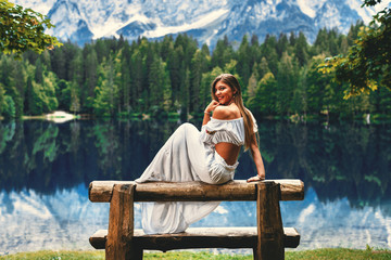 Young beautiful woman sitting on the bench next to the lake