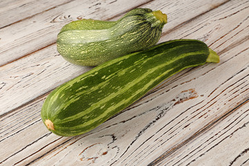 Zucchini on a wooden, white background.