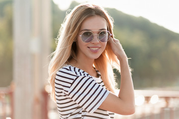 Outdoor shot of glad friendly woman wearing striped attire and round violett glasses. Smiling blonde woman posing with lovely smile in sunny warm day