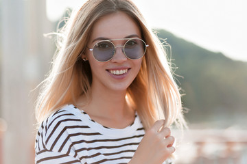 Laughting slim happy woman wears violett glasses looking over shoulder while walking down on the sunny street. Adorable girl in elegant attire enjoying good warm day