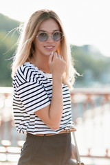 Glamorous blonde woman in modern sunglasses posing at camera in front of shady street. Glad girl spend free time outdoor while walking in park.