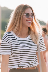 Lovely girl with white teeth and healthy skin posing on the street while chilling outdoor. Close-up photo of happy young lady in summer t-shirt relaxing and has fun outside