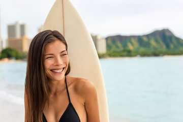 Asian surfer girl smiling portrait. Beautiful surfing woman with surfboard on Waikiki beach, Hawaii, USA travel surf lifestyle.
