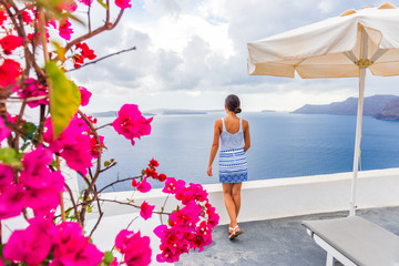 Wall Mural - Santorini Oia hotel luxury resort holiday tourist woman looking at view from balcony - Greece summer travel vacation.