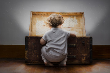 An adorable little child dressed in pajamas with diaper sticking out looks into a mysterious bright treasure chest.
