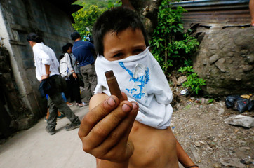 A child displays a bullet casing after clashes with anti-government protesters in the Sandino neighborhood in Jinotega