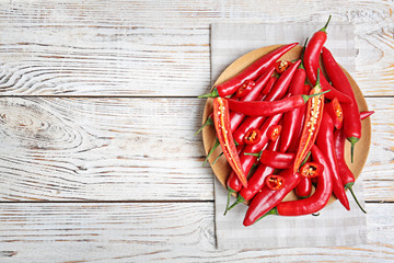 Plate with chili peppers on wooden background, top view