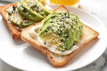 Toast bread with avocado and seeds on plate, closeup