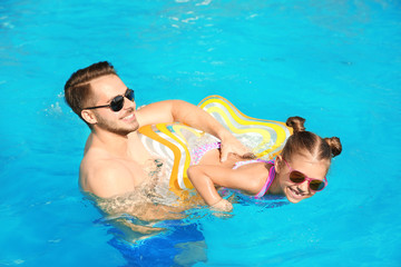Father teaching daughter to swim with inflatable star in pool on sunny day