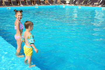 Little children standing in swimming pool on sunny day
