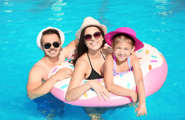 Young family with little daughter in swimming pool on sunny day