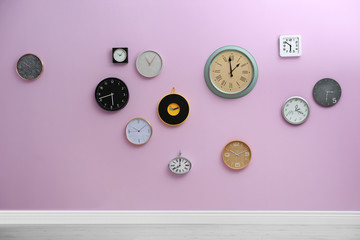 Many different clocks hanging on color wall. Time of day