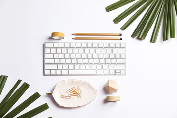 Creative flat lay composition with tropical leaves, stationery and computer keyboard on white background