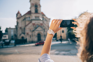 Close-up of young woman traveler making photo of an old church