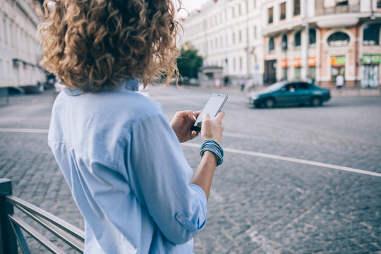 Rear view unrecognizable curly young woman using smart phone