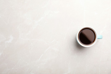 Ceramic cup with hot aromatic coffee on marble background, top view