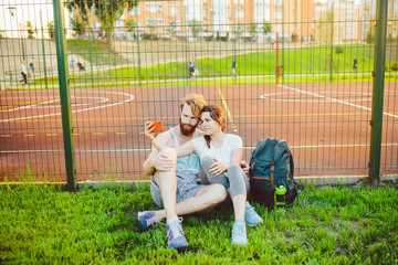 A European man's pair of red hair and a beard and a woman rest after playing sports outdoors. The guy holds a red smartphone on his outstretched hand and takes a photo on the shuttle's front camera