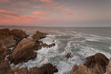 Wide angle landscape image of rock formations and the indian ocean along the Garden Route coast of South Africa