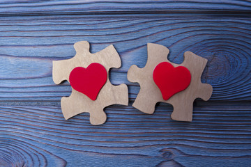 puzzles, two figures of a red heart on a blue wooden background. love, relationship, romance.