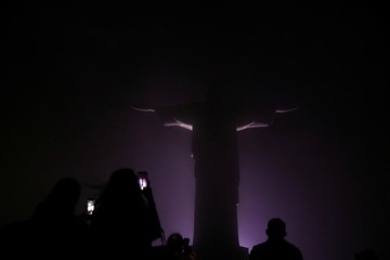 "People wait to photograph the Christ the Redeemer when it is lit up to launch the campaign named ""Movement to Survive,"" to warn elderly people who suffer diabetes about cardiovascular diseases, in Rio de Janeiro"