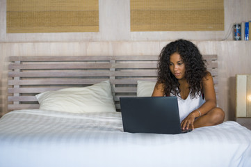 lifestyle portrait of young beautiful and happy black African American woman at home bedroom sitting cheerful on bed networking using laptop computer