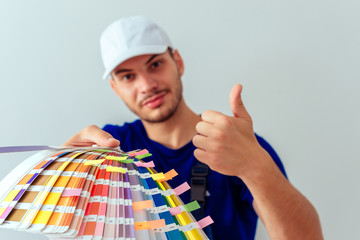 Portrait of uniform man while holding color guide for the wall. Home improvement concept.