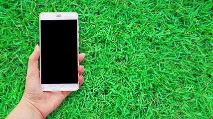 Mockup image of hands holding white mobile phone in green grass background