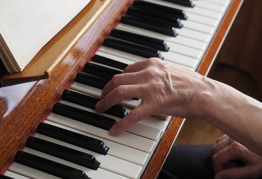 Elderly woman hands playing the piano, close up