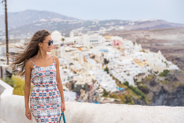 Fototapete - Happy tourist woman walking in the streets of Oia, Santorini, Greece vacation. Europe summer holiday destination.