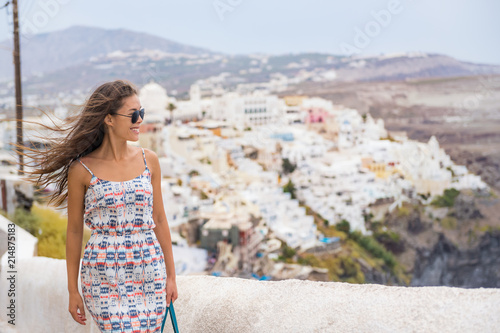 Wall mural Happy tourist woman walking in the streets of Oia, Santorini, Greece vacation. Europe summer holiday destination.
