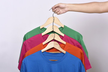Hands holding clothes hook with colored clothes