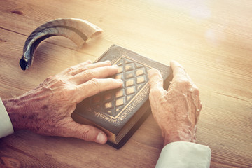 Old Jewish man hands holding a Prayer book, praying, next to shofar (horn). Jewish traditional symbols. Rosh hashanah (jewish New Year holiday) and Yom kippur concept.
