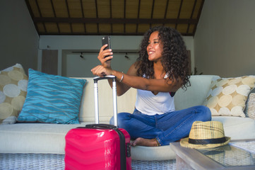young attractive and happy black latin American woman at home with suitcase sitting on sofa couch leaving for holidays trip feeling excited smiling cheerful