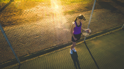 Close up portrait of a female tennis player on a tennis court with beautiful warm back light sunset.