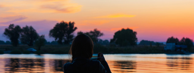 Panorama of girl takes pictures near the lake at the sundown