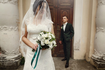 Beautiful newlywed brunette bride under veil in white wedding dress posing with roses bouquet near old column building, handsome groom in the background